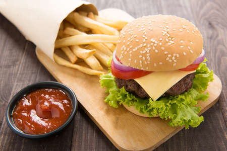 burger background: hamburger with french fries on wooden background. Stock Photo