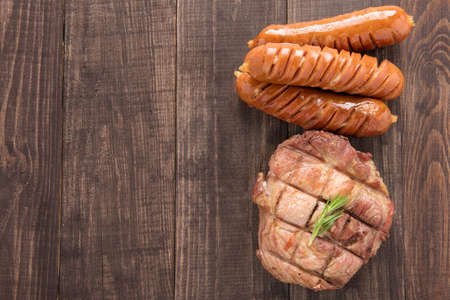 wooden table top view: Top view grilled steak and sausage on a wooden background.