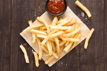 view from the above: French fries with ketchup on wooden background.