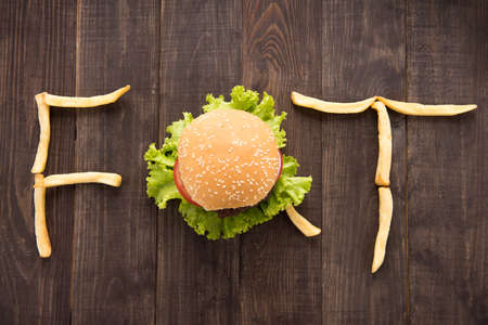 inventive: French fries with burger forming word fat on wooden background.