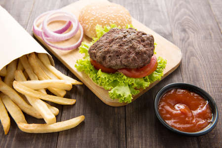 burger: hamburger with french fries on wooden background. Stock Photo