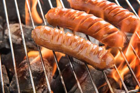 embutidos: Asar salchichas en llamas en la parrilla. Foto de archivo