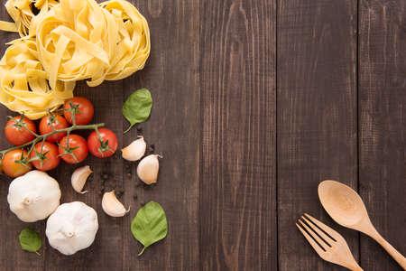 cocineros: Ingredientes de las pastas. tomate, ajo, pimiento y champiñones en el fondo de madera.