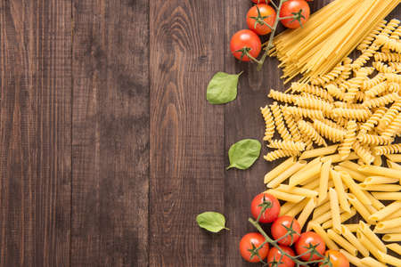 wood table: Mixed dried pasta selection on wooden background. Stock Photo