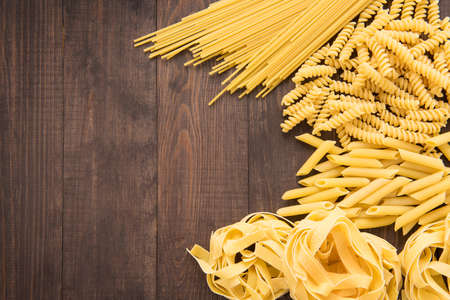 Mixed dried pasta selection on wooden background. Stok Fotoğraf