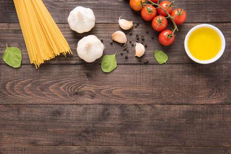 パスタの食材。トマト、ニンニク、唐辛子、油、木製の背景にキノコ。