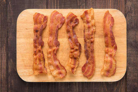 Fried bacon strips on the wooden board.