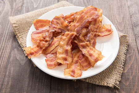 Closeup of fried bacon strips on white plate.