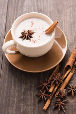 masala chai: Masala chai with spices cinnamon, cardamom, ginger, clove and star anise on wooden background. Stock Photo