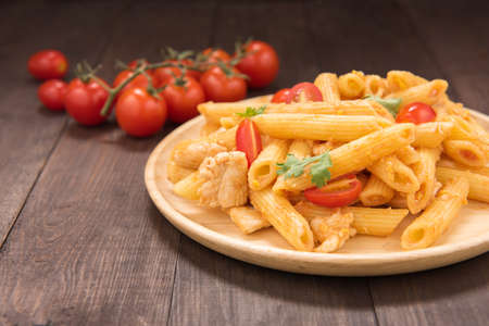 gastronomy: Penne pasta in tomato sauce with chicken on a wooden table.