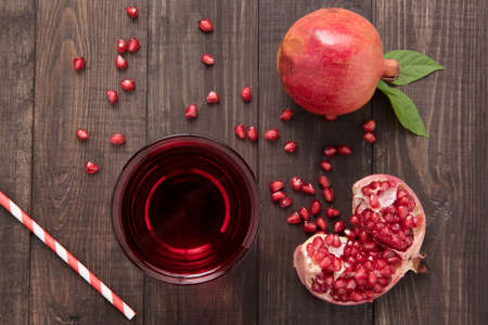 Ripe pomegranates with juice on wooden background. Banco de Imagens