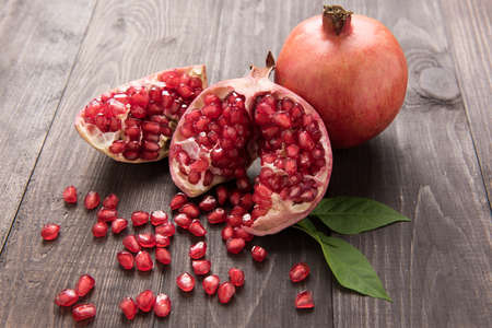 Ripe pomegranate fruit on wooden vintage table.