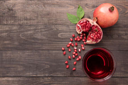 Ripe pomegranates with juice on wooden background. Stock Photo