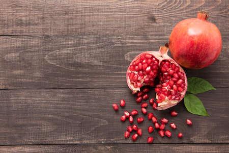 jugo de frutas: Fruta madura de la granada en el fondo de madera de la vendimia. Foto de archivo