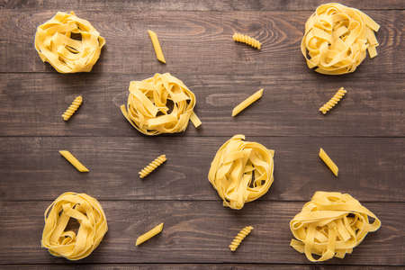 mixed wallpaper: Pasta shapes collection on a wooden background. Stock Photo