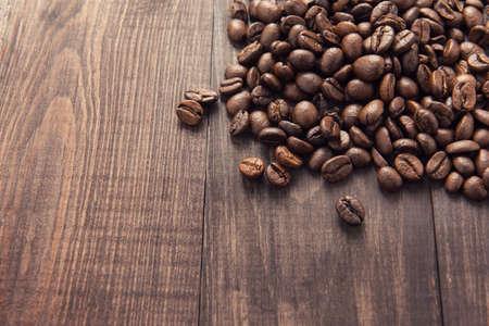 planta de cafe: los granos de caf� tostado en el fondo de madera.