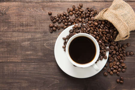 morning coffee: Coffee cup and coffee beans on wooden background. Top view.