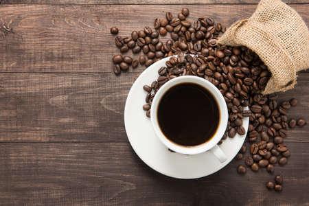 copa: Taza de café y granos de café sobre fondo de madera. Vista superior.