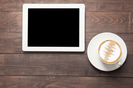 Digital tablet and coffee cup on wooden background.