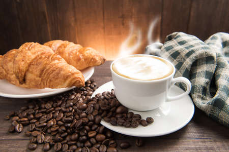 capuchino: Desayuno taza de café y croissant en el fondo de madera. Foto de archivo