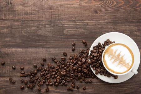 grano de cafe: Taza de café y granos de café sobre fondo de madera. Vista superior.