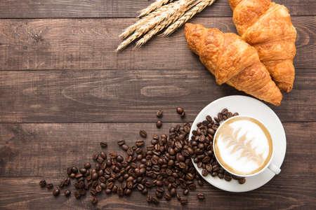 granos de cafe: Taza de café y croissants recién horneados sobre fondo de madera. Vista superior.