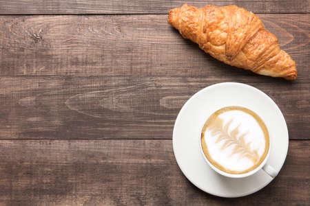 コーヒー カップと木製の背景に焼きたてのクロワッサン。平面図です。