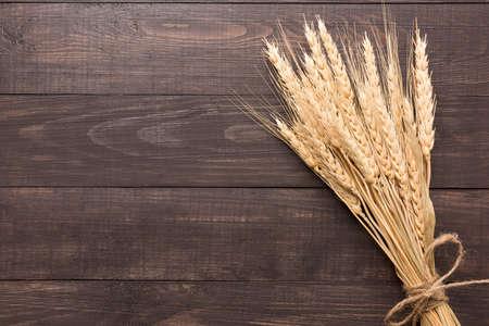 木製の背景に小麦の穂。平面図です。