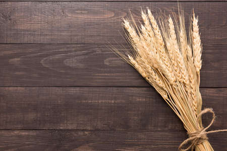 Wheat ears on the wooden background. Top view. Archivio Fotografico