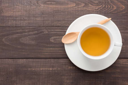 Ginger tea with spoon on the wooden background.