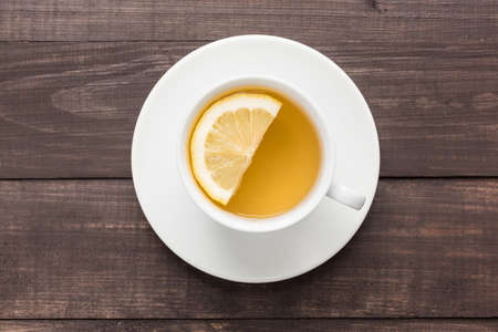 taza de té: El té de jengibre con limón en el fondo de madera.