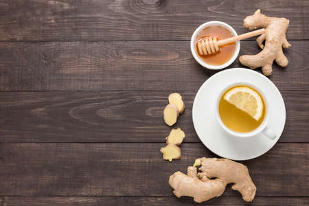 fresh ginger: Cup of ginger tea with lemon and honey on wooden background. Stock Photo