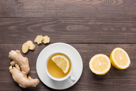 lemon water: Ginger tea with lemon on the wooden background. Stock Photo