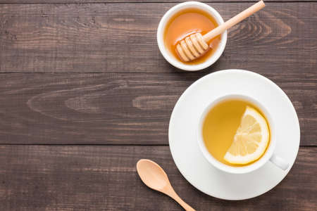 lemon water: Tea with lemon and honey on the wooden background.