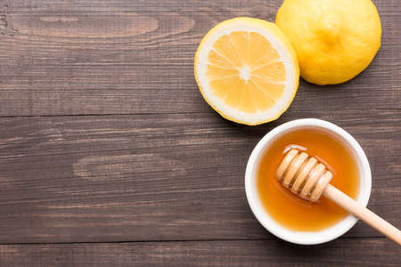honey pot: Bowl of sweet honey and lemons on wooden table.