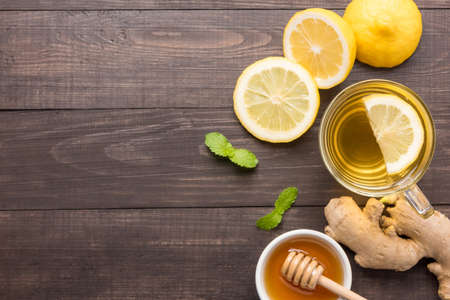 Cup of ginger tea with lemon and honey on wooden background. 免版税图像