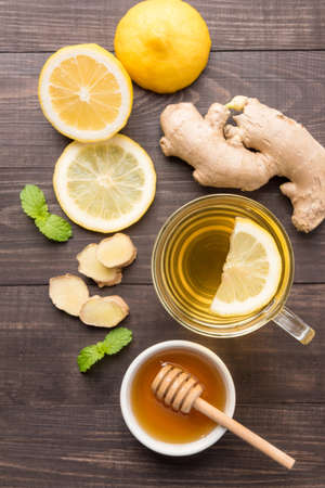 Cup of ginger tea with lemon and honey on wooden background. Standard-Bild
