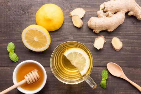 木製の背景の上に蜂蜜とレモン ジンジャー ティーのカップ。