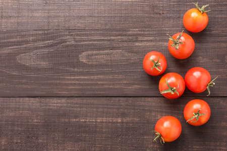 tomatos: Fresh tomato on the brown wooden background. Top view. Stock Photo
