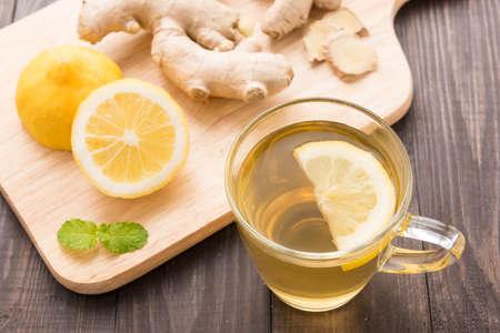 木製の背景にレモンと生姜のお茶のカップ。