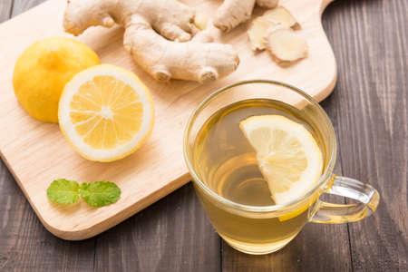 Cup of ginger tea with lemon on wooden background.