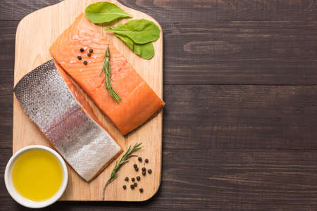 salmons: Fresh salmon fillet with spice on wooden background.