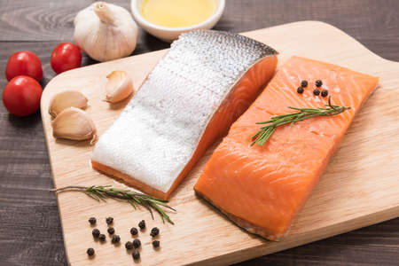 Fresh salmon fillet with spice on wooden background.