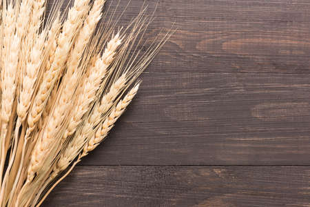 ears: Wheat ears on the wooden background. Top view. Stock Photo