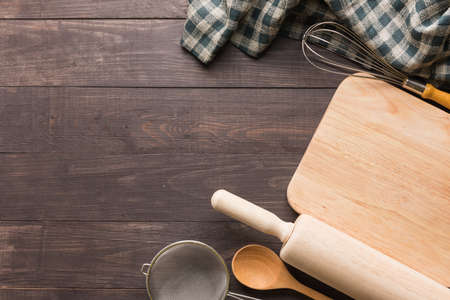 Wooden kitchen tools and napkin on the wooden background.