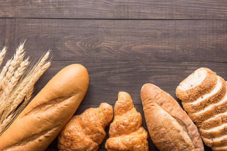 baked bread: Fresh baked bread and wheat on wooden background.