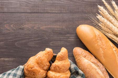 焼きたてのパンや小麦の木製の背景。