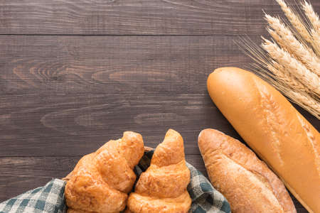 Vers gebakken brood en tarwe op de houten achtergrond.