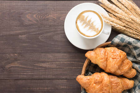 pasteleria francesa: Taza de café y croissants recién horneados sobre fondo de madera. Vista superior.