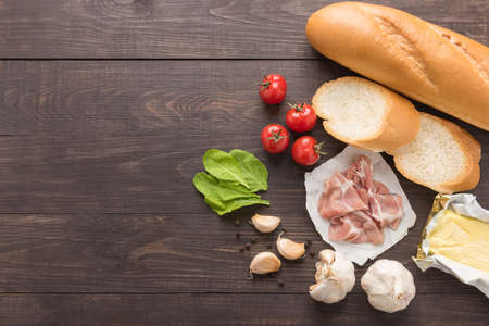 baguette: Ingredients for sandwich with smoked meat, baguette on wooden background.